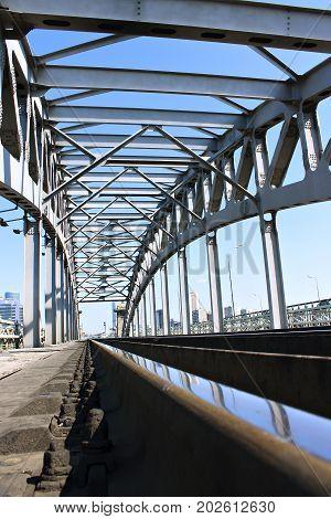 Steel railway bridge spans against the blue sky