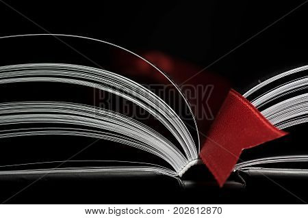 A black and white image of open book. Close-up image of double-page spread with red bookmark on black background. Concept of gaining knowledge learning typography passion for reading