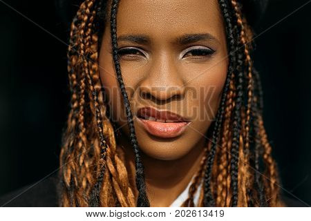 Impudent African American woman. Stylish hair. Insolent facial expression on black background, modern youth lifestyle, cocky concept