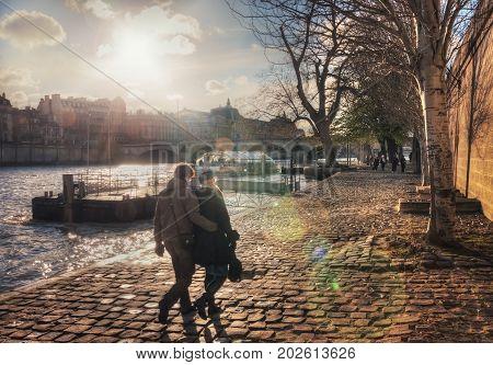 France, Paris - March 2008: Couple walks on the quai des Tuileries at sunset. France. Paris.