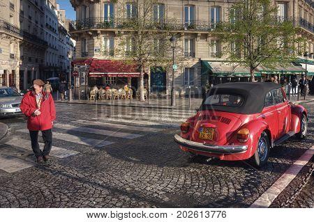 An elderly tourist in a red jacket strolls past a red old car. Crossroads of Rue Saint-Louis en l'Ile, Rue Jean du Bellay and Quai de Bourbon. France. Paris