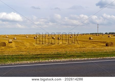 agricultural landscape of the field with straw bales after harvesting of cereals and a part of the highway in the photo from a retro effect