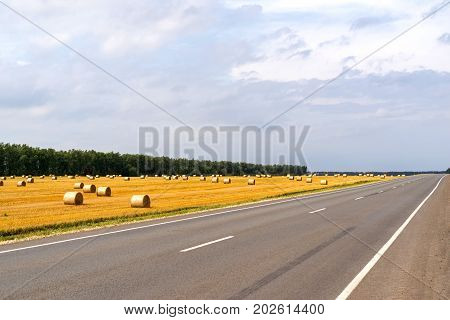 landscape of the agricultural field after harvesting of cereals with sheaf of straw and the highway