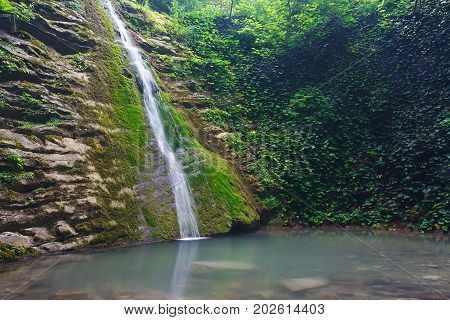 Cliffs covered with ivy and moss with a waterfall flowing down
