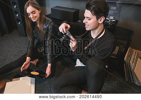 Happy young people take picture of their hobby. Love for retro vinyl records. Modern youth lifestyle, creative pastime together