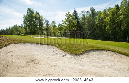 golf trap, golf bunker with sand rake, raking the sand on a sunny day