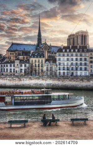 France, Paris - March 2008: Two girls on the quai de l'Hotel-de-Ville and tourist ship, overlooking the quai Bourbon and Notre-Dame. France. Paris