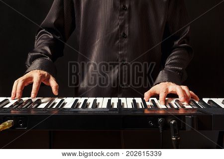 Musician playing the electronic synthesizer on a black background