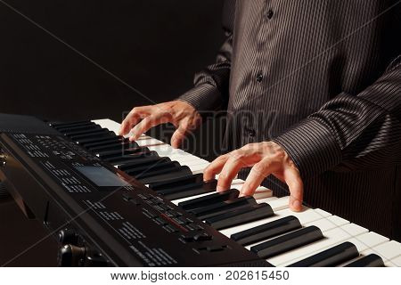 Musician play the keys of the electronic organ on a black background