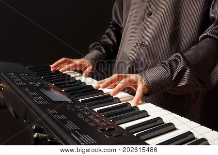 Pianist playing the synth on a black background