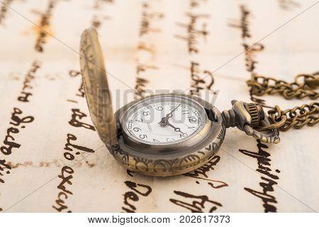 Vintage pocket watch over old manuscript background