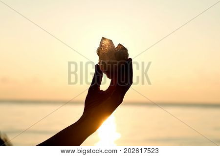 Young woman's hands holding clear quartz point in front of the lake sunrise