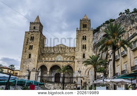 main church of cefalu with its particular architectural style buildings of the city and the famous rock formation of the city behind the church