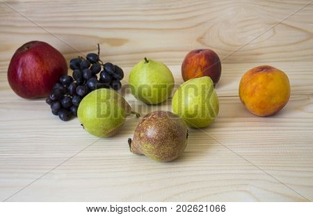 Fresh fruits. Healthy food. Mixed fruits are grapes, pears, peaches. eat, diet, like fruit. Studio photography of various fruits on an old wooden table. Organic healthy assorted fruits.
