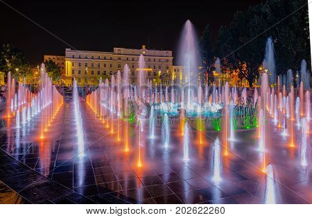 Night colorful fountain show inLublin park. Vivid color fountain water