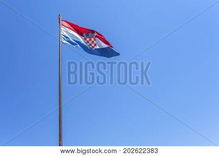 Flag of Croatia flying on a sunny day against a blue sky.