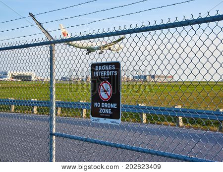 MONTREAL CANADA - AUGUST 28 2017 : No drones zone sign and airplane at Montreal YUL airport.