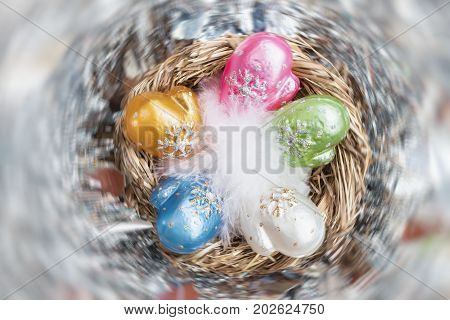 Christmas decoration from colorful decorative celluloid mittens with white bird fluff in nest. Element of Christmas design, holiday decorations