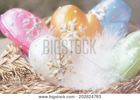 Christmas decoration from colorful decorative celluloid mittens with white bird fluff in nest