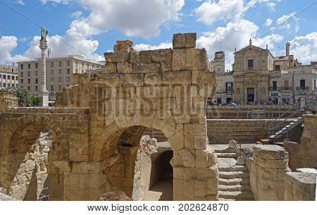 LECCE ITALY - JULY 27 2017: the Ancient Roman amphitheater and the Piazza San Oronzo with is monumental column in the background