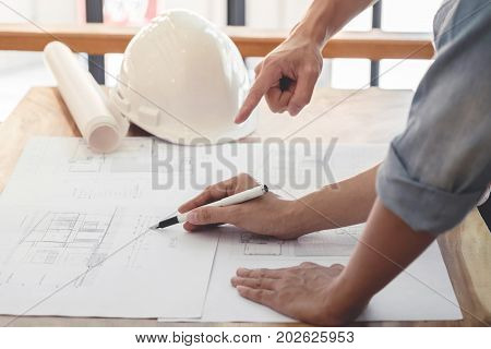 Image of engineer or architectural project Close up of hands architects engineering working on blueprint with engineering equipment tool Construction concept.