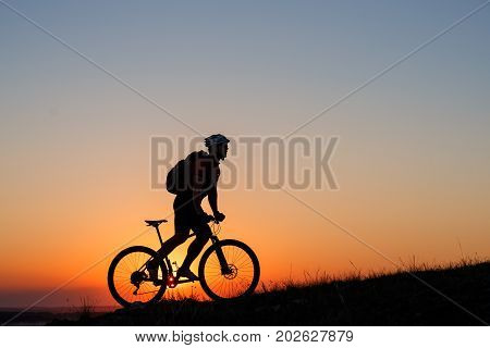 Silhouette the man stand in action with mountain bike on the meadow against sunset