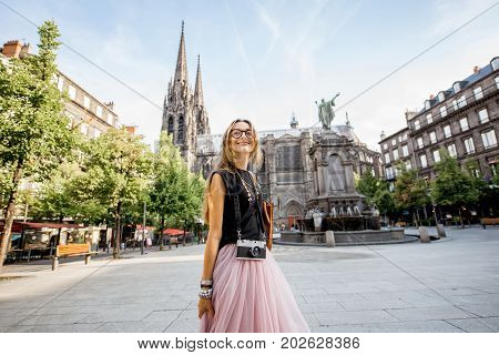 Lifestyle portrait of a woman traveling in front of the famous cathedral in Clermont-Ferrand city in France