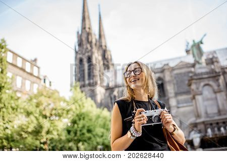 Portrait of a woman with photo camera traveling in front of the famous cathedral in Clermont-Ferrand city in France