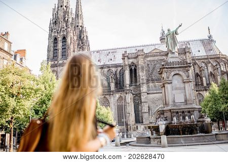 Woman enjoying morning view on the famous cathedral in Clermont-Ferrand city in France. Woman is out of focus
