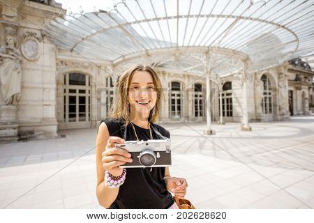 Young woman tourist with photo camera standing near the old Opera building in Vichy city in France