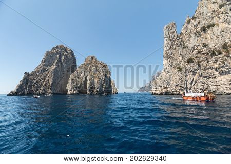 CAPRI ITALY - JUNE 13 2017: View from the boat on the Faraglioni Rocks on Capri Island Italy.