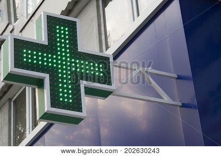 Pharmacy Neon Sign. Green сross sign on the building. Pharmacy concept. Drug store.