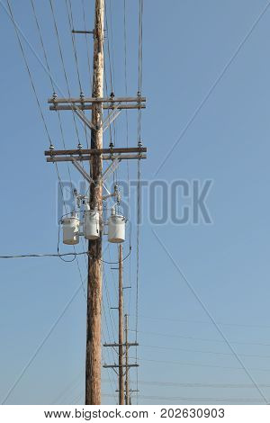 Wooden power utility pole and clear and cloudy blue sky.