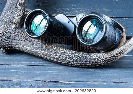 Binoculars and deer horn. Binoculars for tourists and hunters. Compass for tourist.