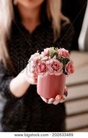 Young woman holds crimson cup with roses in hands. Concept of love, romantic gift and happiness, holidays and congratulations, St.Valentine's day, Mother's day