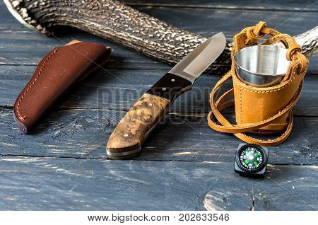 Knife with a fixed blade and leather sheath near deer horn. Hunter accessories.