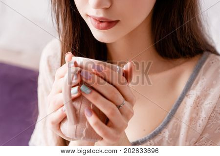 Sensitive young unrecognizable woman delights her morning coffee. Meeting sunrise with favorite aromatic drink, enjoyment and calmness concept, positive beginning of day, close up picture