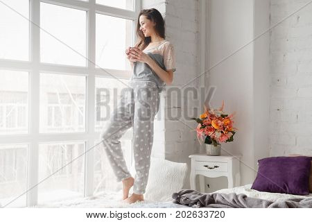 Joyful young woman staying on sill near panoramic window at home with cup of coffee. Enjoyment and calmness, relaxation and good mood concept. Positive start of the day