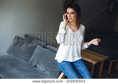 Good Talk. Attractive Young Smiling Woman Talking On Smart Phone And Gesturing While Sitting In Rest