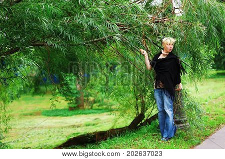 Young beautiful smiling girl in blue jeans and a black tippet is near a tree on a summer day in the Park.