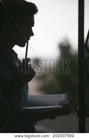 Young thoughtful reader. Pensive poet. Attentive unrecognizable male, dark creative atmosphere, education concept