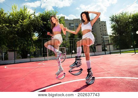 Two Friends Jumping And Fun In Kangg Jumping Shoes. Girls Holding Hands And Posed In Kangoo Jump Sho