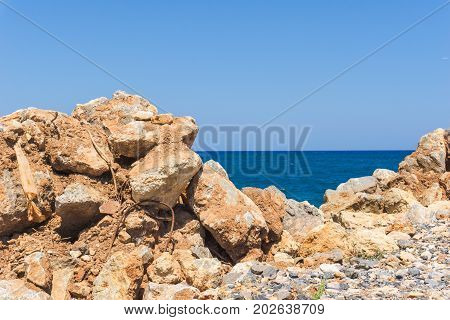 View on a turquoise Ocean in front of a clear Sky. Close-up of colorful Stones in front of a blue Sea Beach and Nature Background.