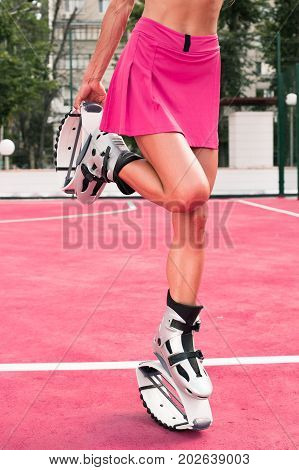 Fit Legs In Kangoo Jumping Shoes. Short Skirt, Beautiful And Sexy Girl Do Sport Kangoo Exercises On