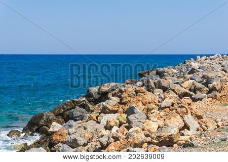 View on a turquoise Ocean in front of a clear Sky. Close-up of a Rock on front of a blue Sea. Beach and Nature Background.