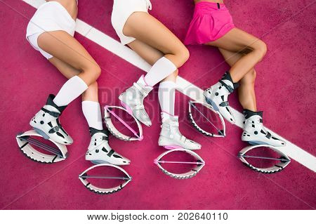 Three Sexy Legs Of Girls Laying On The Pink Background And Sexy Exercises Of Legs In Kangoo Jumps Sh