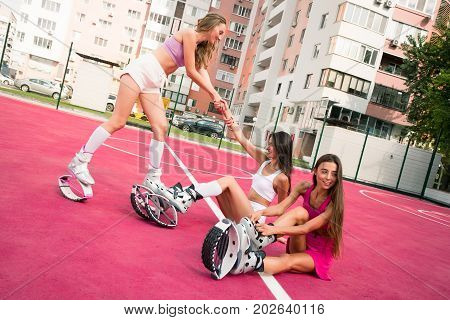Friend Help To Her Friend Get Up And Lough After Hard Working Training. Another Young Girl Preparing