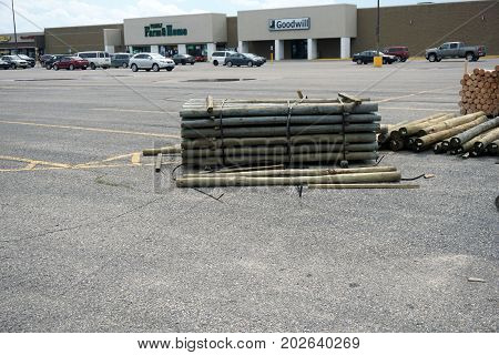 CADILLAC, MICHIGAN / UNITED STATES - JUNE 22, 2017: Treated landscape timbers, offered for sale by Family Farm and Home, are piled in a corner of the parking lot of the Village at Wexford Shopping Center on Mitchell Street.