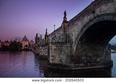 Twilight violet picture of the oldest bridge in Prague Czech republic: Charles Bridge. Medieval gothic bridge over the river of Vltava with baroque statues.