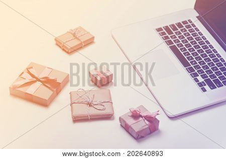 Beautiful Gifts Of Different Sizes And Cool Laptop On The Wonderful Pink Background
